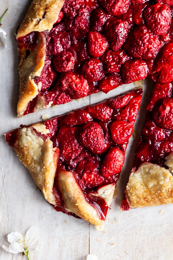 Close up view of a slice of strawberry galette sitting on a piece of parchment paper