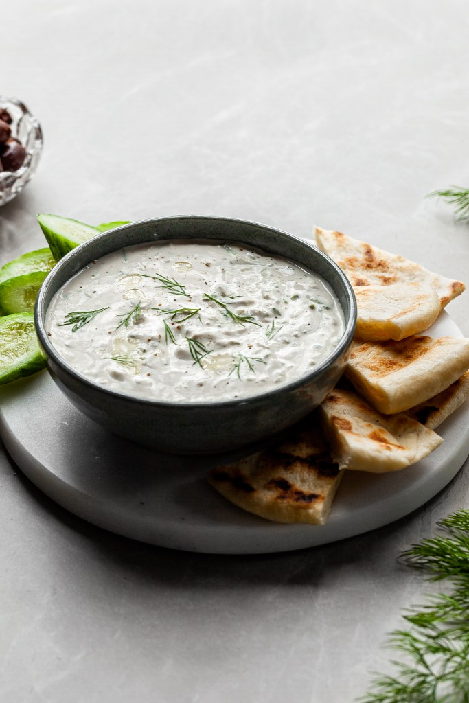 vegan tzatziki in a bowl served with flatbread and a small bowl of olives in the background