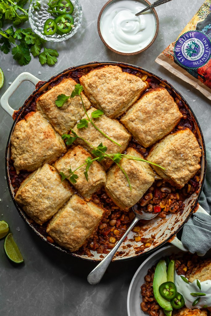 Vegan chili pot pie in a white enamel skillet with a bowl just served and garnished with vegan sour cream sliced green onion and fresh jalapeno slices