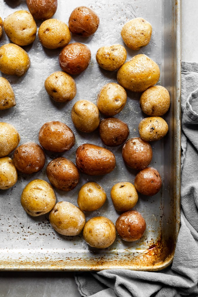 Yellow and red baby potatoes on a baking tray