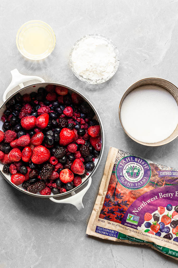A white pot filled with a mixture of frozen berries, a bowl of sugar, cornstarch and lemon juice beside a bag of Stahlbush Island Farms Northwest Berry Blend