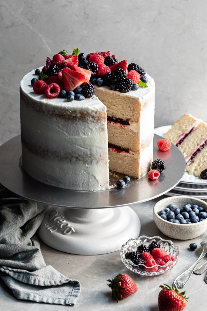 Triple layer vanilla cake layered with fruit filling with a slice cut. A plate in the background with the cut slice of cake.