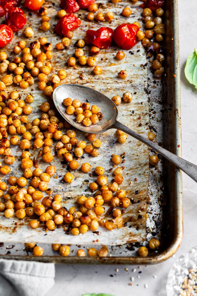 Roasted chickpeas and cherry tomatoes on a baking sheet