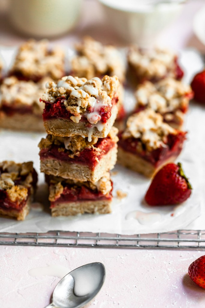 Stack of 3 strawberry crumble bars with fresh strawberries in the background