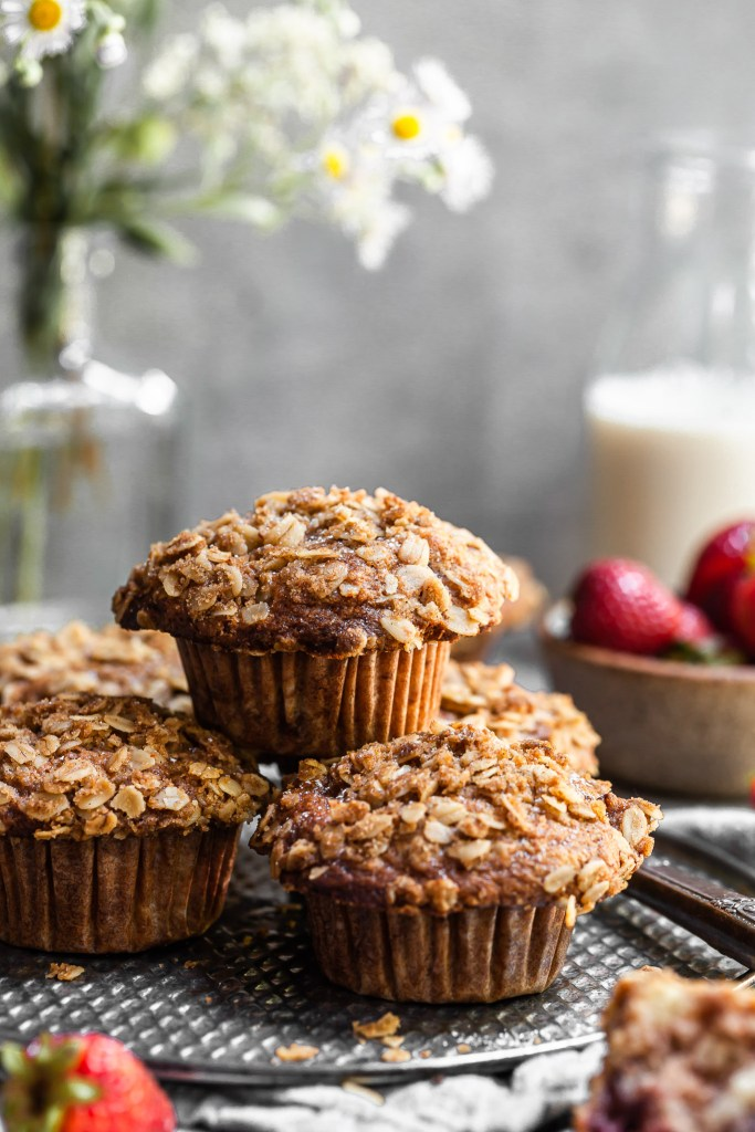 Fresh muffins stacked on an antique tray with a bottle of soy milk and a bowl of strawberries in the background