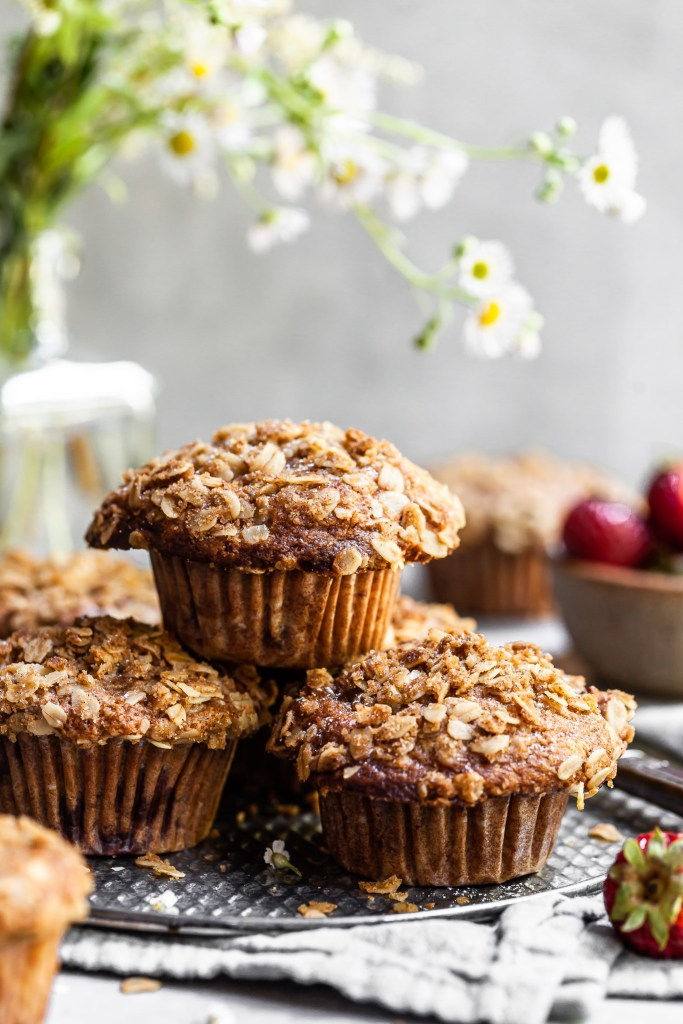 Stack of oat topped muffins on a grey platter with a bowl of strawberries in the background