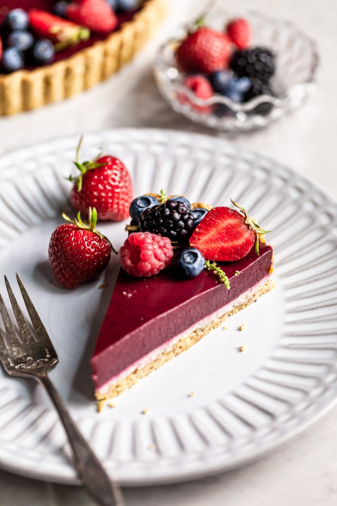 Slice of a layered tart - bottom is shortbread lined with white chocolate and then a layer of purple berry curd. Garnished with berries, served on a white plate.