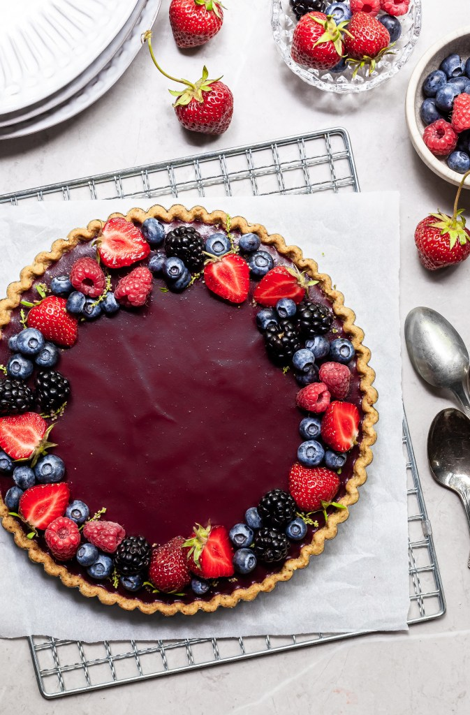 flatlay of a purple berry tart, garnished with summer berries, and several small bowls with berries beside it