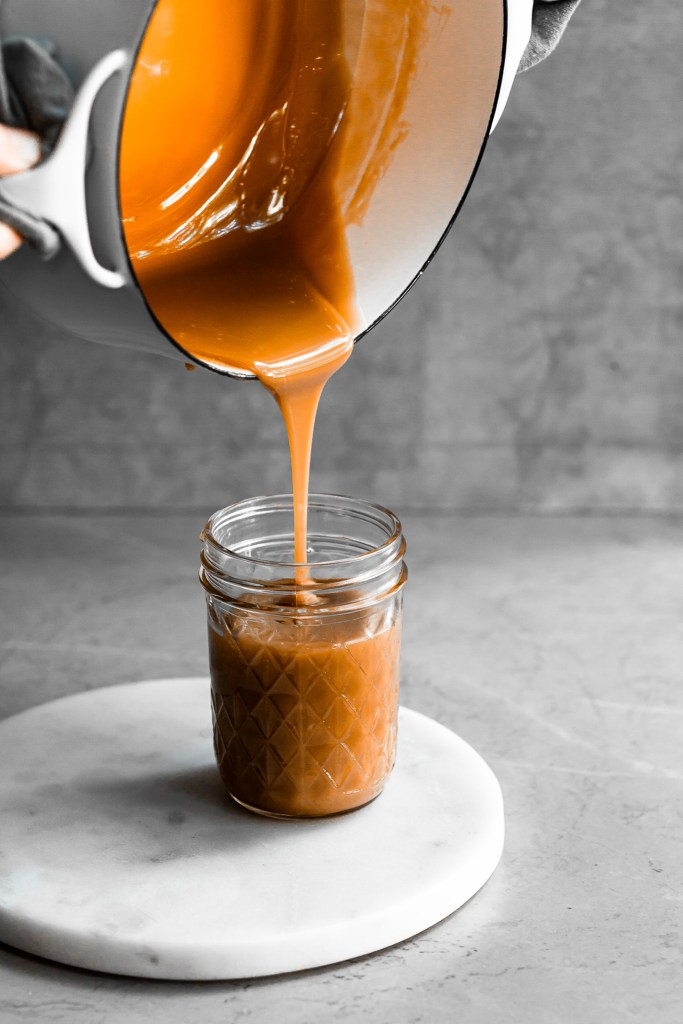 caramel being poured from a white pot into a clear glass jar
