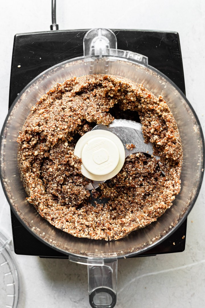 view into a food processor filled with blended up pecans and dates ready to be pressed into tart pans