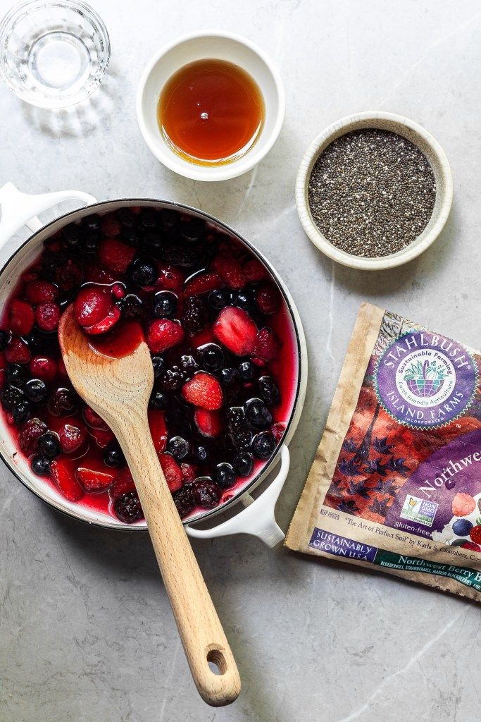 a white pot filled with a berry blend and water, with a small bowl of chia seeds, another containing maple syrup and another filled with vanilla extract