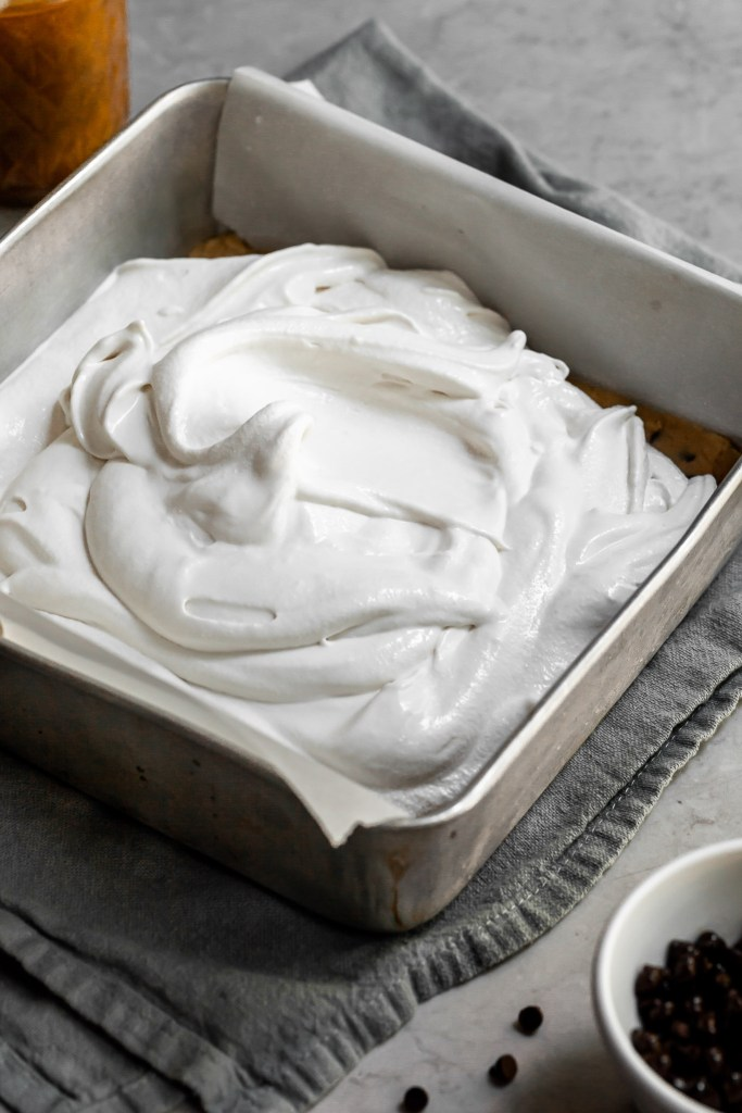freshly churned vanilla ice sits piled in a square baking tray over a layer of cookie dough