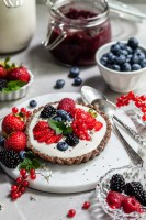 Breakfast table scene with a small tart willed with yogurt and topped with fresh berries