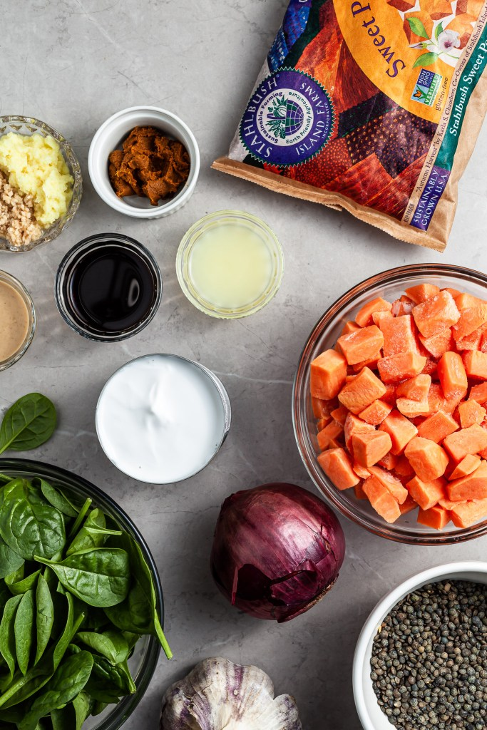 All of the ingredients set out on a marble countertop for the sweet potato lentil curry
