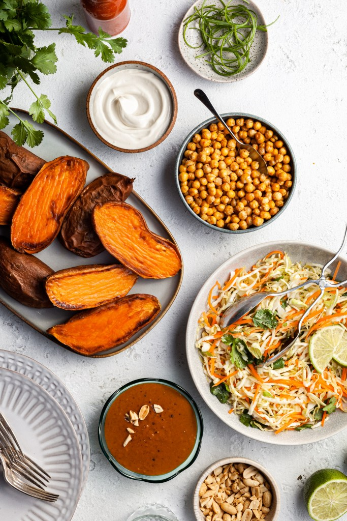 View looking down on the elements of this loaded sweet potato recipe before the sweet potatoes are plated - a platter of baked sweet potatoes, a bowl of coleslaw, a bowl of peanut sauce, a bowl of crispy chickpeas and various garnishes.