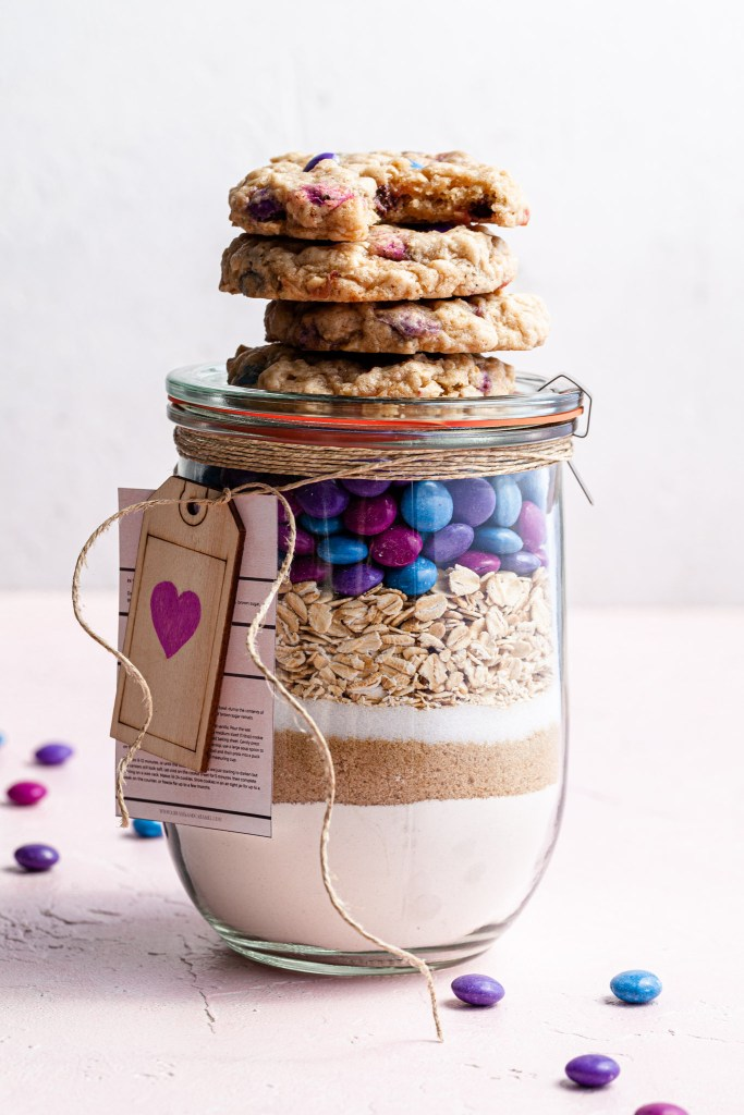 A jar filled with cookie mix, topped with baked vegan m&m cookies.