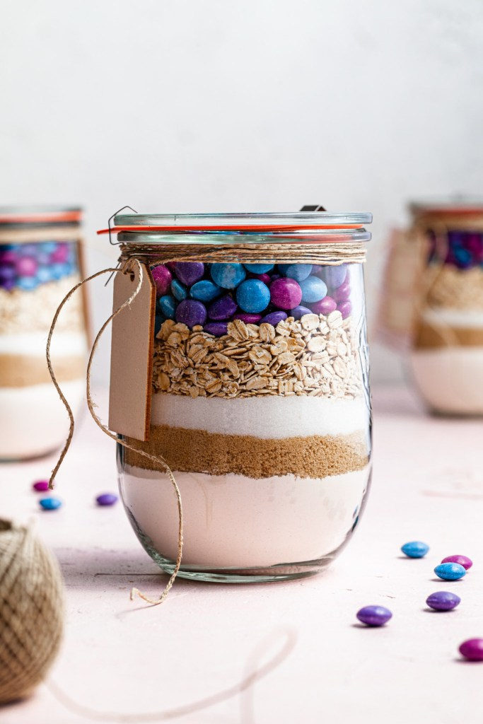 A close up of a jar filled with M&M Oatmeal Cookie mix, wrapped with twine. In the background there are 2 other cookie mix jars.