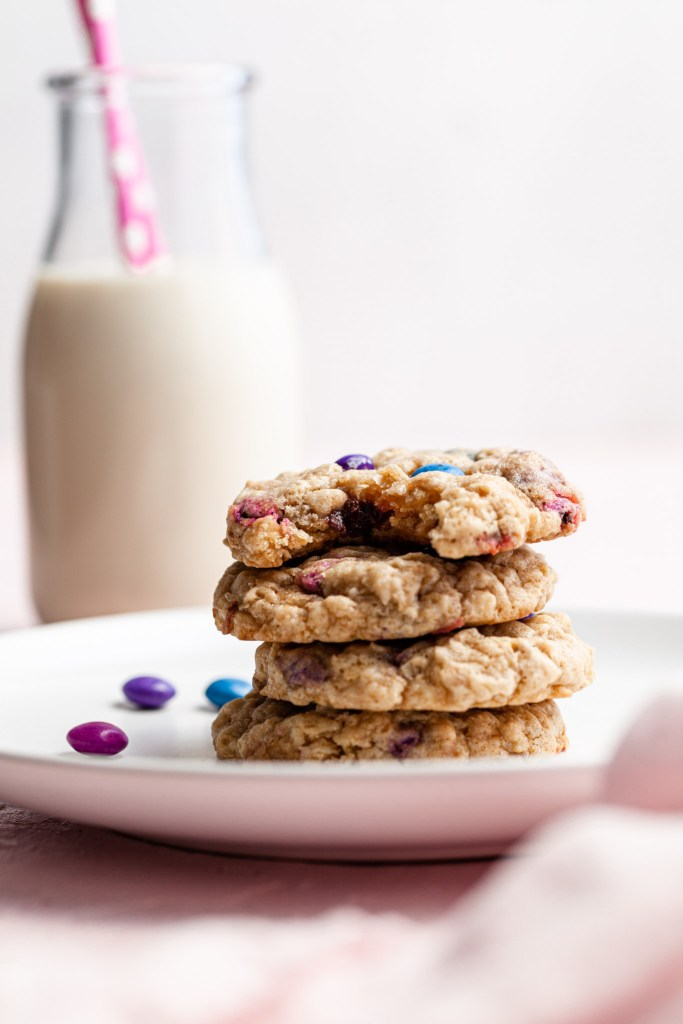 A stack of oatmeal M&M cookies on a white plate . A bottle of milk with a pink straw is in the background.
