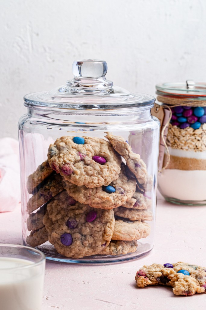 A glass cookie jar filled with cookies, one cookie sits on the counter with a bite missing and a cookie kit jar in the background.