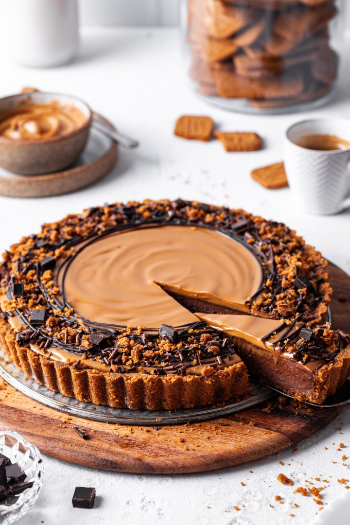 A Vegan chocolate biscoff tart with one slice cut and partly removed to reveal the inside of the tart showing off the chocolate layer topped with cookie butter.