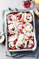 Aluminium baking pan filled with rapsberry sweet rolls covered in vanilla glaze