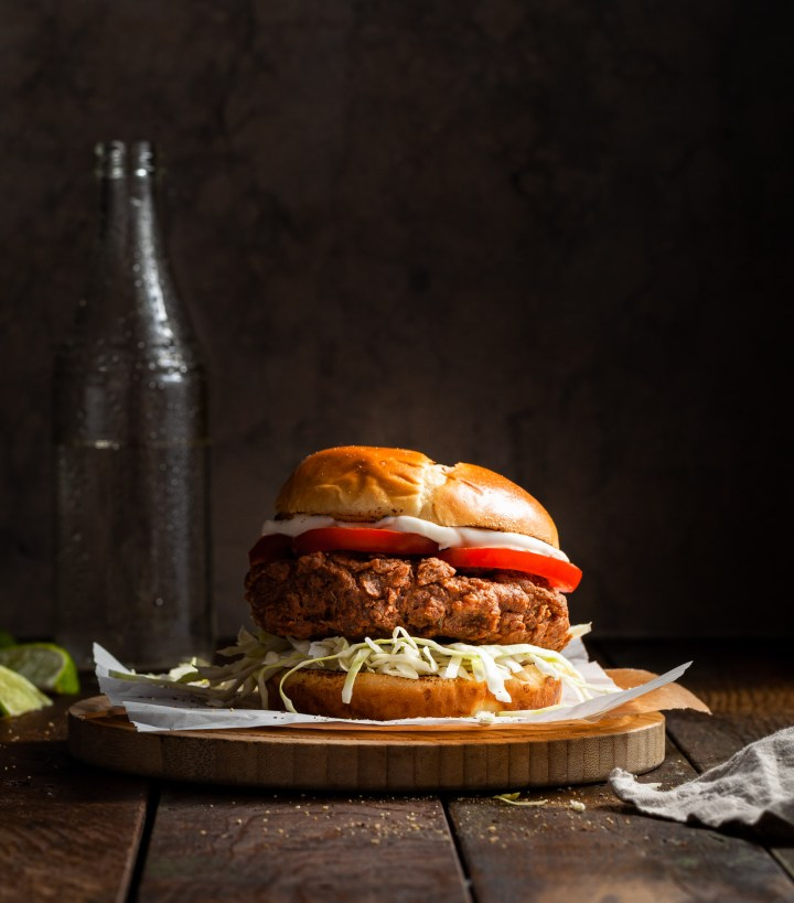 A crispy burger dressed with shredded cabbage and tomato slices on wooden plate with a cold bottled drink in the background.