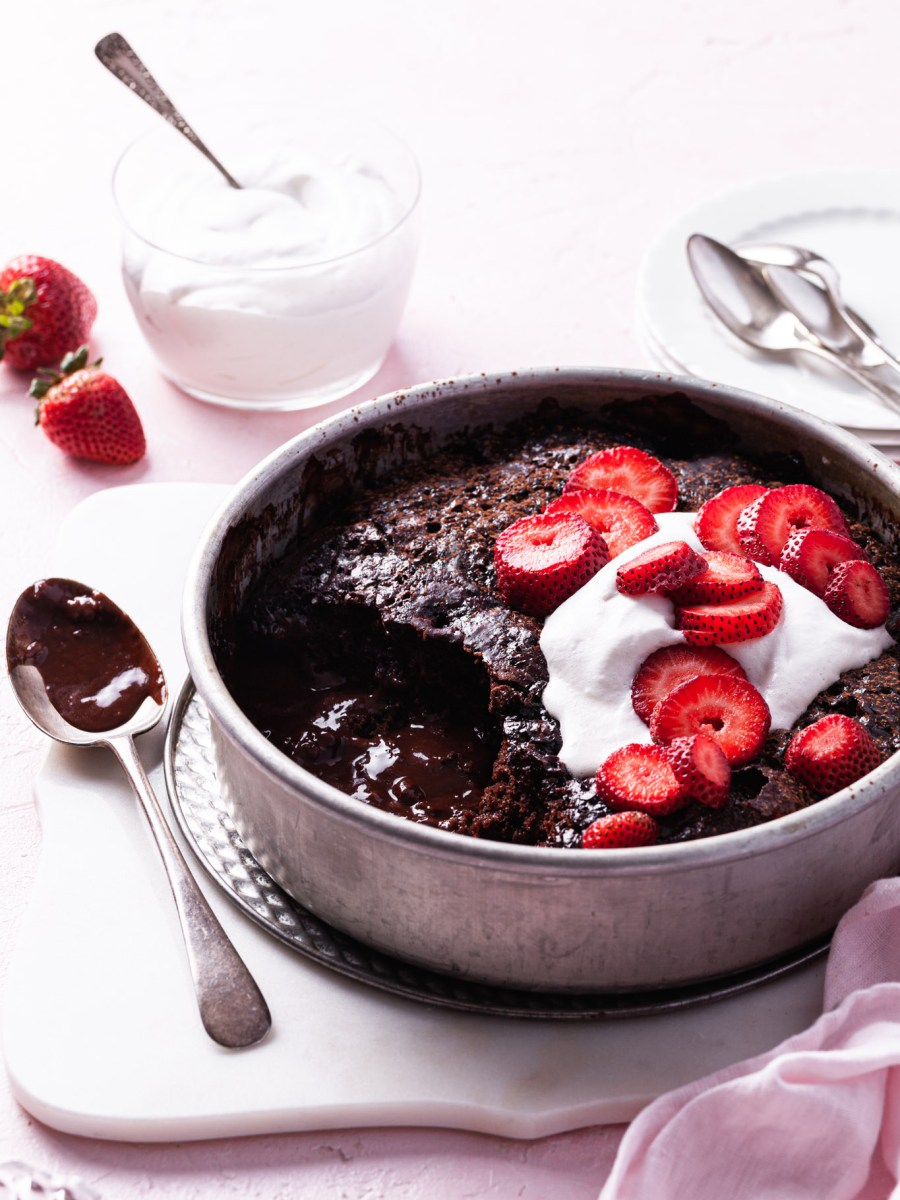 A round cake pan filled with a partially served chocolate cake exposing chocolate sauce on the bottom. Garnished with whipped cream and sliced strawberries.