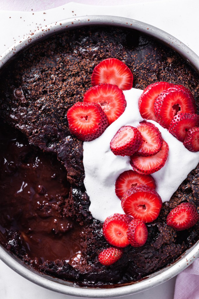 Close up of the self-saucing chocolate strawberry pudding cake with a serving missing so that both the cake and the sauce are visible. The top of the vegan dessert is topped with non-dairy whip and fresh sliced strawberries.