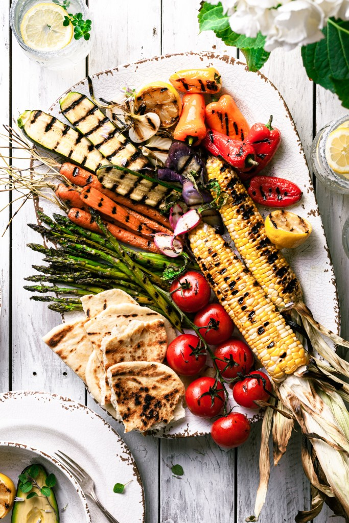 A platter of grilled vegetables on a white picnic table.