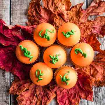 A group of pumpkin spice cupcakes on maple leaves