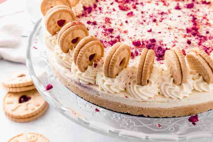 Cheesecake decorated with mini biscuits and raspberry powder