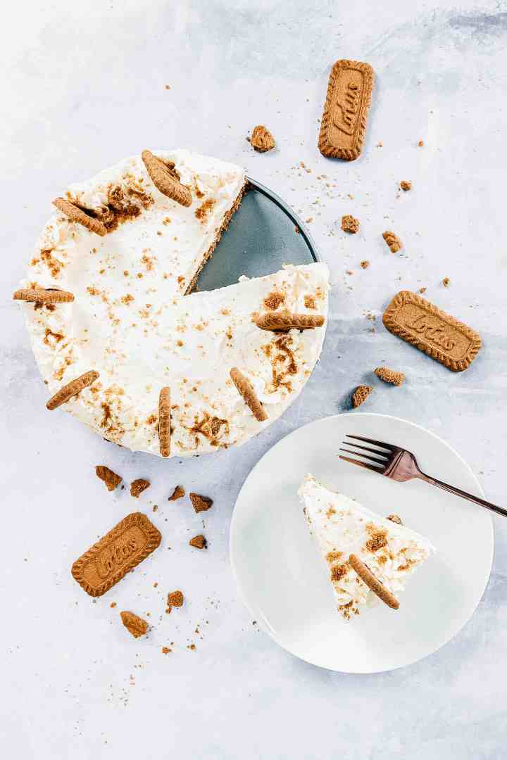 Biscoff cheesecake on a table next to a white plate scattered with biscuit crumbs