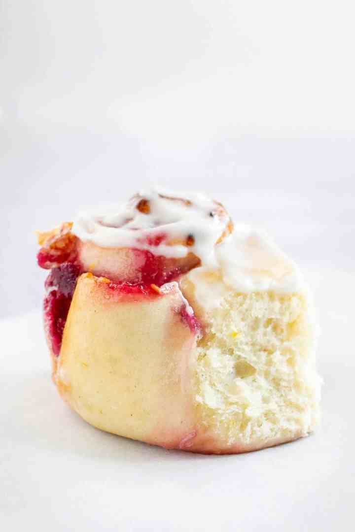 Close up of lemon raspberry swirl roll filled with raspberry jam and iced with white glaze icing