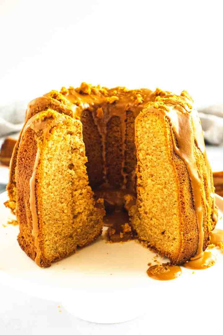 Circular cake drizzled with caramel Biscoff glaze with a slice cut out