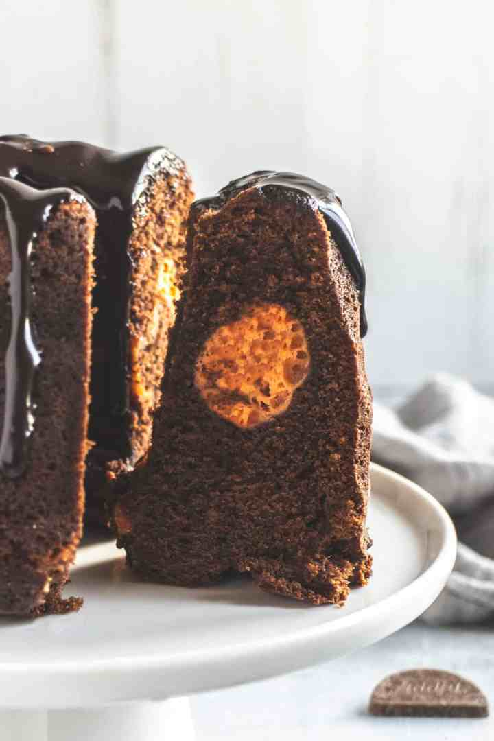 Chocolate cake with a slice cut out, stuffed with orange cheesecake filling