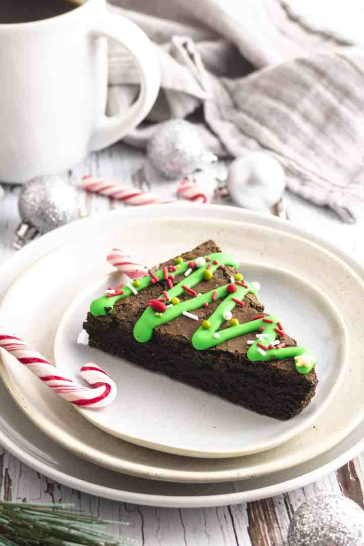 Triangle brownie on a plate with a coffee cup, silver baubles and candy canes