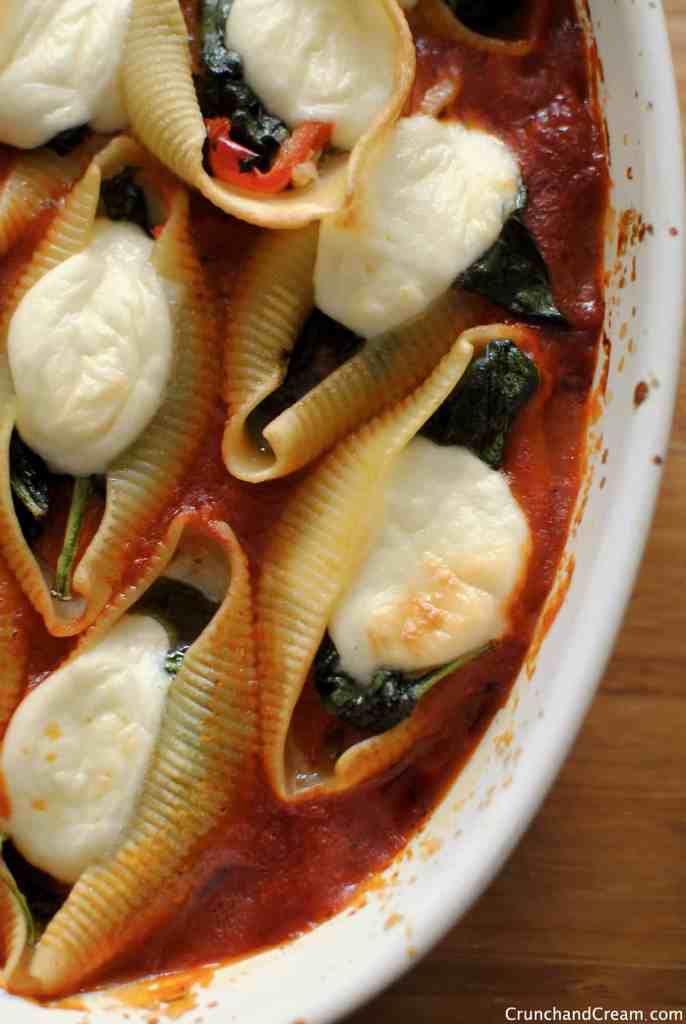 overhead photo of stuffed pasta shells with spinach, pesto, peppers and mozzarella in a casserole dish