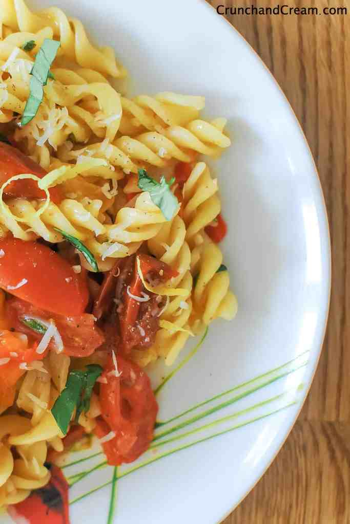 overhead image of half a plate of fusilli pasta in a pile mixed with cooked tomatoes and diced chilli peppers, lemon zest and fresh herbs