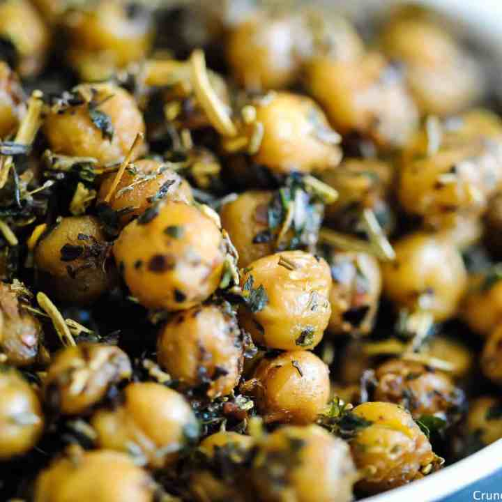 close-up side-on of golden, crispy roasted chickpeas covered in Italian herb seasoning