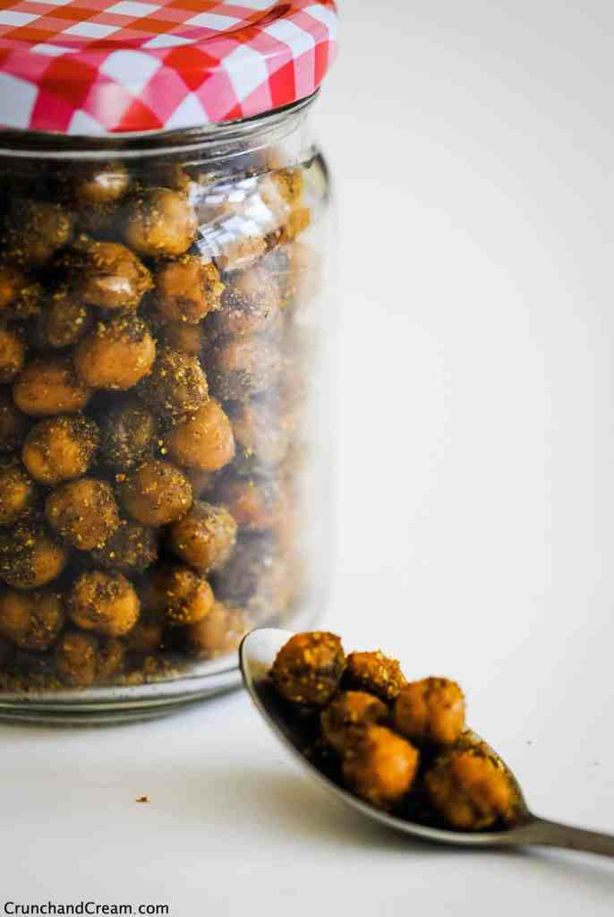 a spoonful of indian chickpeas on a white table in front of a jar full of crispy indian chickpeas