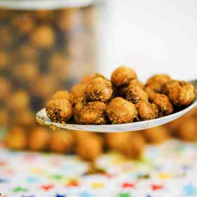 a spoonful of Indian-spiced roasted chickpeas in front of a jar full of them