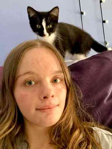 Photo of a smiling 18-year-old with brown hair and a black and white cat behind her