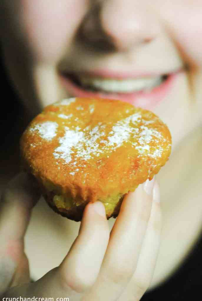 a young girl about to eat an eggless citrus olive oil cupcake dusted with icing sugar