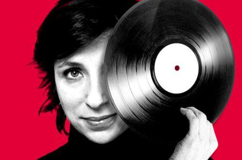Rebecca Manzoni sur un fond rouge avec un vinyle devant son oeil.