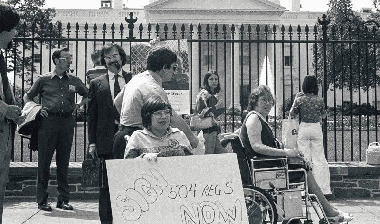 Judy Heumann and other protestors outside of the Whitehouse for 504 activism.