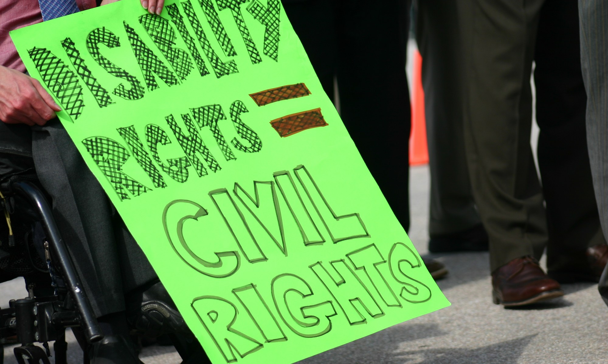 """A person in a wheelchair holding a sign that reads """"Disability Rights = Human Rights"""