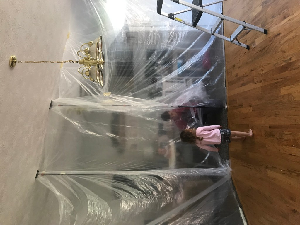 little girl standing on sanded hardwood floor with plastic sheeting taped up  around it to keep dust out