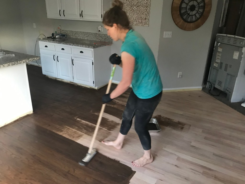 Girl in green shirt staining hardwood floor Minwax dark walnut mixed with Classic Gray