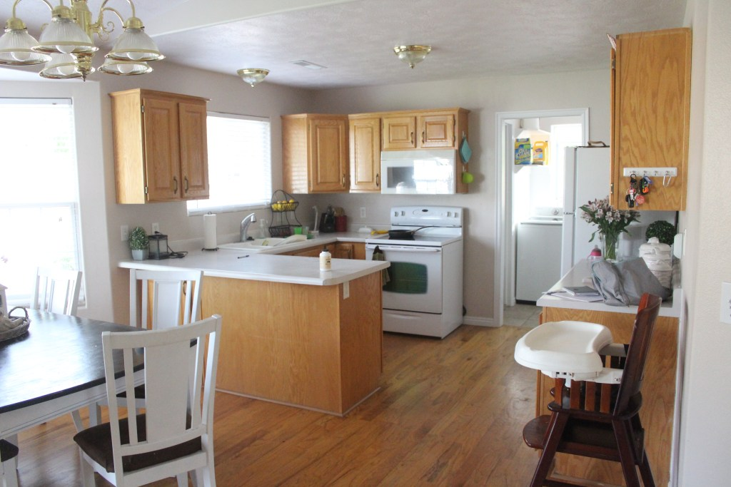 Kitchen before it was painted with Natural Oak cabinets and flooring that has yellowed over time