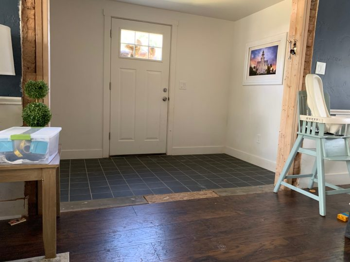 Entryway before build with black tile flooring and plain white walls